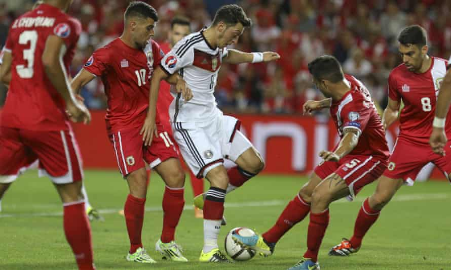 Mesut Özil is tackled by Gibraltar's Ryan Casciaro during the Group D Euro 2016 qualifier at the Algarve stadium, Portugal.