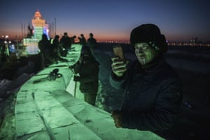 A worker takes a picture of the ice sculptures he and others have built