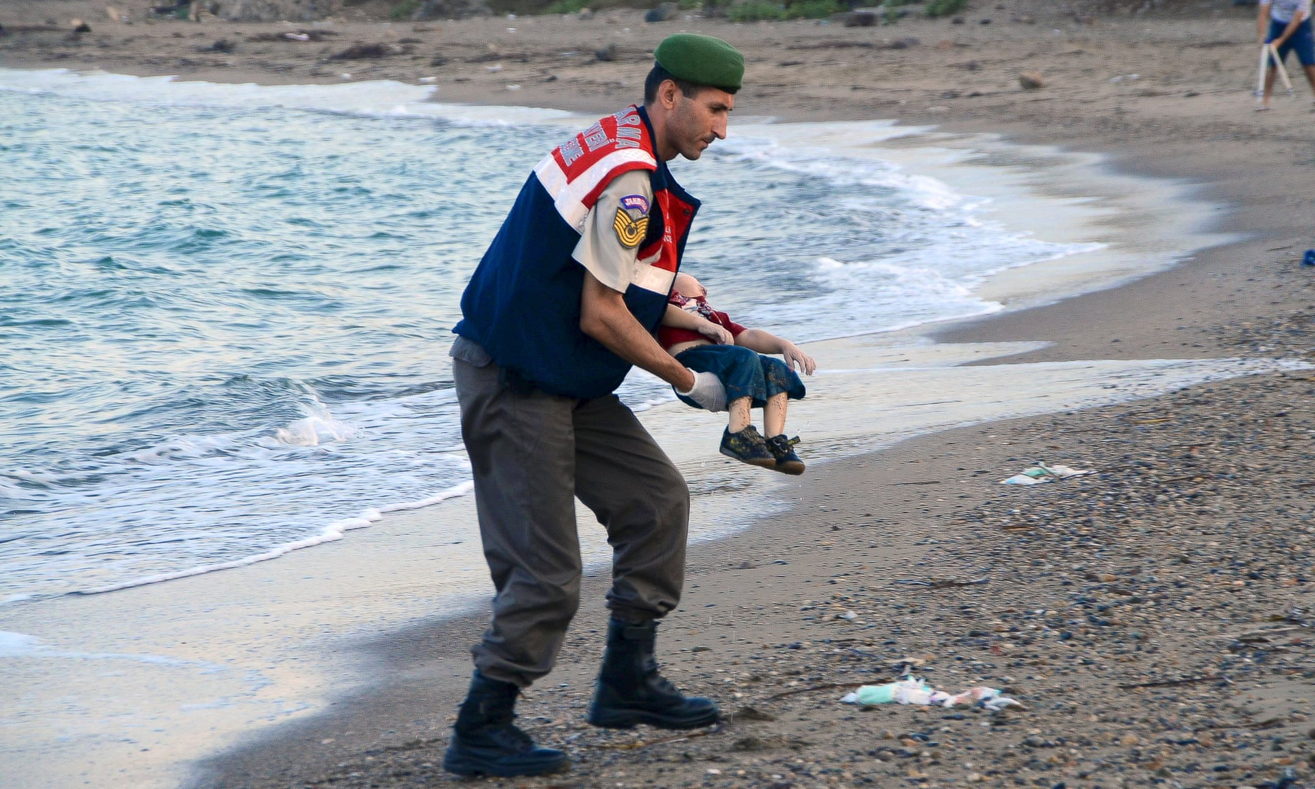(A Turkish police officer carries the body of Aylan Kurdi who drowned in a failed attempt to sail to the Greek island of Kos © Reuters)