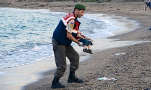 A Turkish police officer carries a young drowned boy