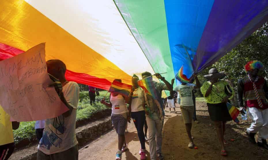 The 2015 Pride Uganda parade, under a giant raiblow flag, in Entebbe