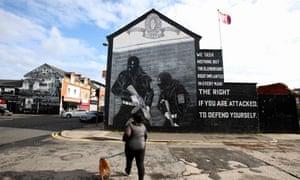 A pedestrian walks past a Loyalist Ulster Volunteer Force (UVF) mural on the Newtownards road in east Belfast
