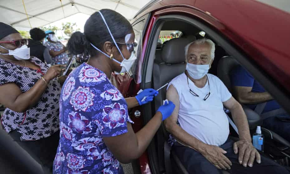 Miguel Garcia, 78, right, prepares to receive a dose of the Pfizer's Covid-19 vaccine, at the Miami-Dade County Tropical Park vaccination. Some are calling for age limits on vaccine eligibility to be lifted as younger people are more likely to spread the virus.