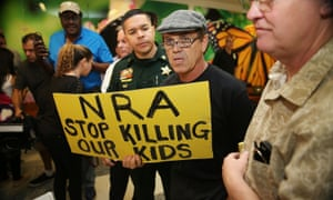 A protester holds a sign that reads, 'NRA Stop Killing Our Kids', outside the court-room where Nikolas Cruz, 19, a former student at Marjory Stoneman Douglas High School in Parkland, Florida, was having a bond hearing.