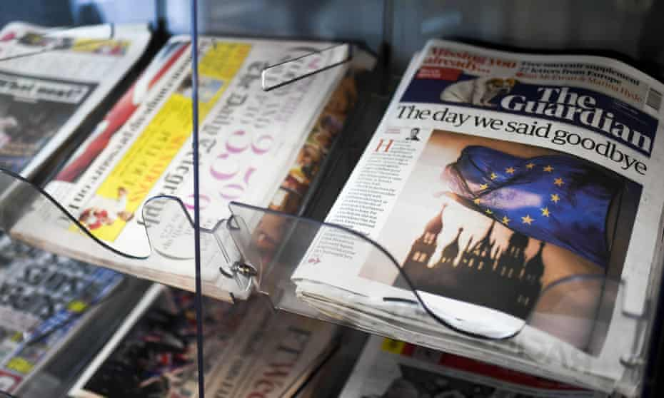 The Guardian on a news stand next to other newspapers