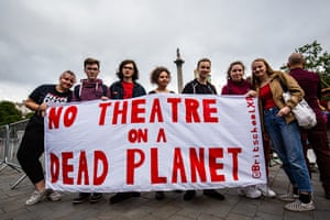 Protesters hold up banner that says No theatre on a Dead Planet