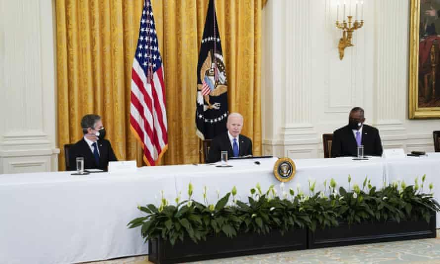 Joe Biden speaks during a cabinet meeting in the East Room of the White House as Antony Blinken, left, and Lloyd Austin, right, listen.