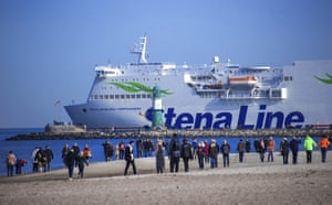 Warnemuende, Germany: People walk on the beach as a ferry leaves the port of Rostock