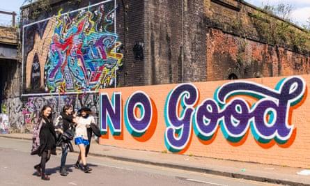 Three women walking in front of graffiti