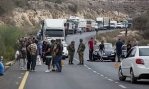 Palestinians wait at an Israeli checkpoint near the scene of a shooting attack at Barkan industrial zone in the West Bank
