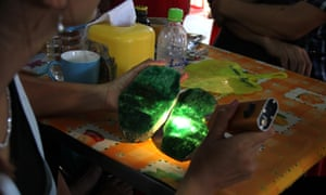 A woman examines the quality of a jade stone from the Hpakant mine area.