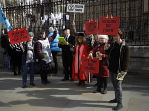 Extinction Rebellion protesters hold a demonstration against the budget outside parliament in London.
