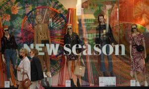 Shoppers walk past a shop window display