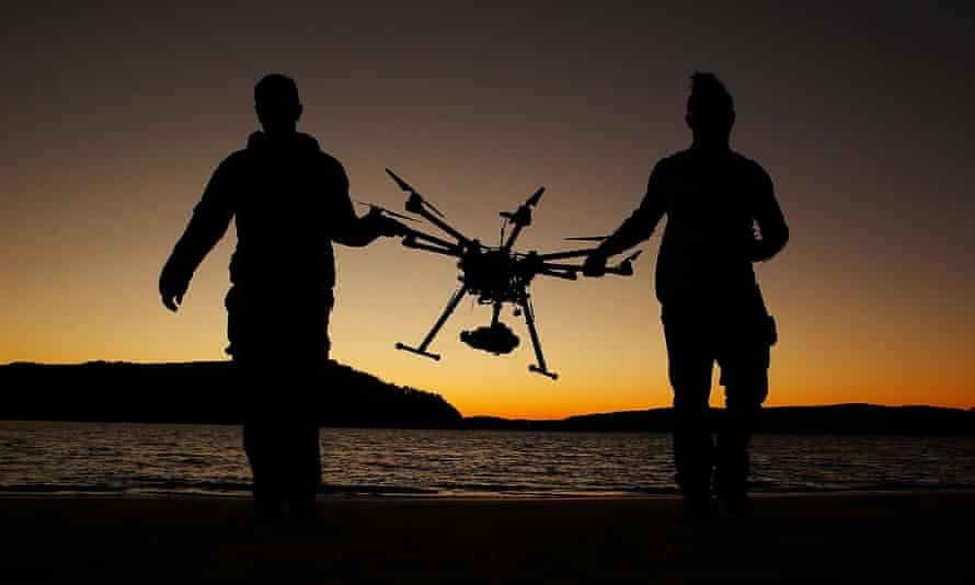 Two men carrying a commercial drone