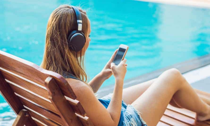Woman relaxing near swimming pool listening with earbuds to streaming music and on a phone.