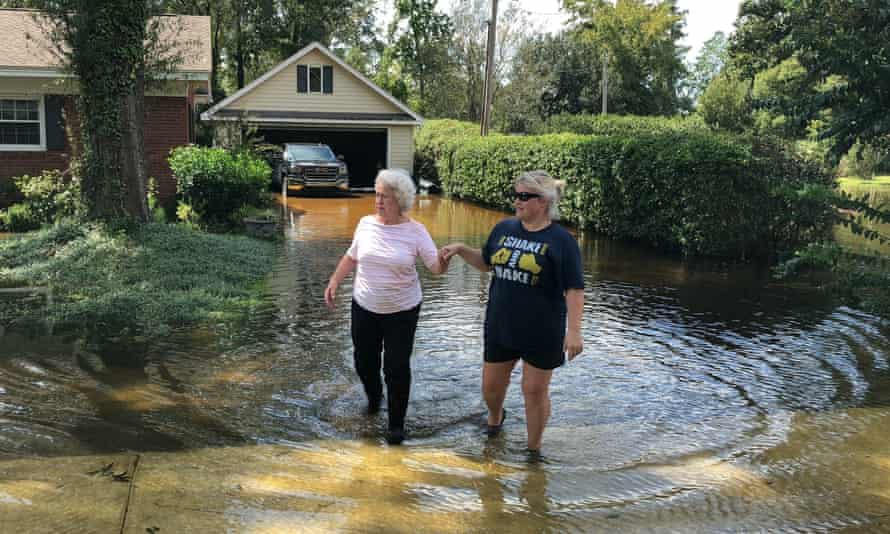 Vivian Chestnut, left, and her neighbor Morgan Sellers walk through floodwaters around Chestnut's home in Conway, South Carolina, on Monday.