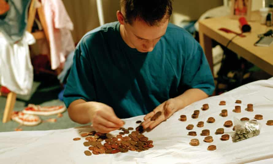 Yong man counting coins on a bed