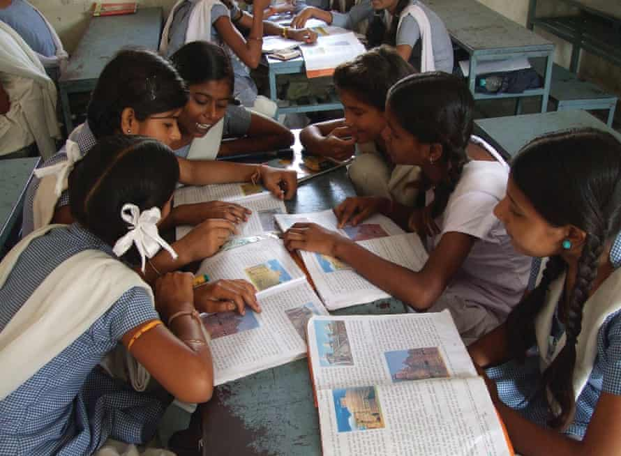 A group of school children in a classroom in India discuss their work