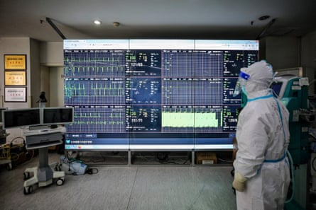 A medical staff member monitors a screen that shows figures of patients infected by the Covid-19 coronavirus at a Red Cross hospital in Wuhan.
