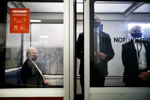 Mitch McConnell, left, wears a face mask as he rides the Senate subway between meetings on Capitol Hill on 21 July