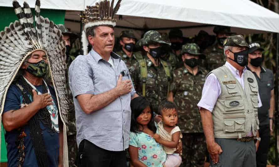 President Jair Bolsonaro listens to national anthem next to an indigenous person at the Yanomami tribe reservation bordering Venezuela in São Gabriel da Cachoeira, Amazonas state, Brazil, on Thursday.