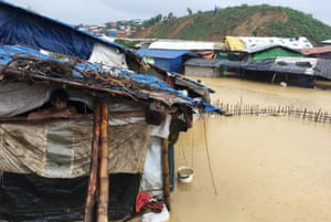 Abdul Hakim, a Rohingya refugee, looks on as his shelter is flooded during heavy rain in Cox's Bazar, Bangladesh