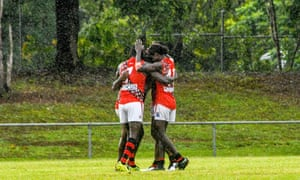 Simon Munkara, Michael Cooper and Austin Wonaeamirri embrace after the sealing goal against the Crocs