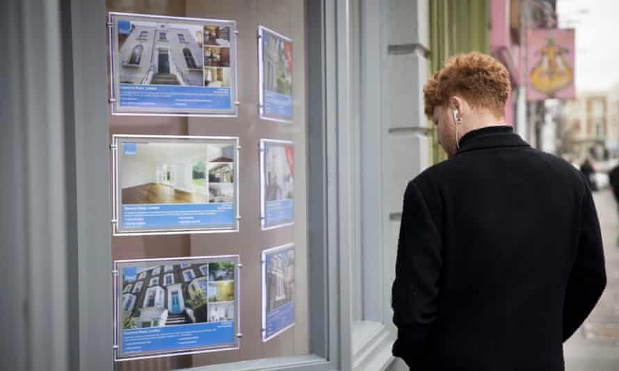 A man looks in the windows of an estate agency in north London
