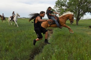 Mahto in the Woods leaps over a small creek on foot while his cousin Jayden Lookinghorse jumps over on his horse on the Cheyenne River Reservation in Green Grass, South Dakota