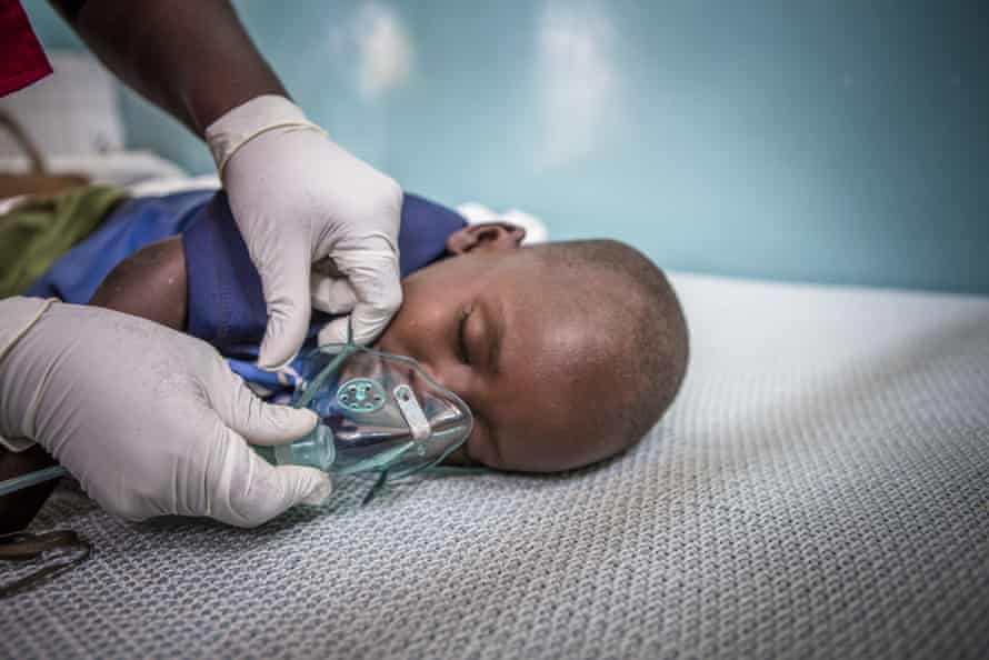 Save the Children emergency health officer Jedidah Onyango fits an oxygen mask to three year-old pneumonia patient Jackson at Turkana County referral hospital, Kenya.