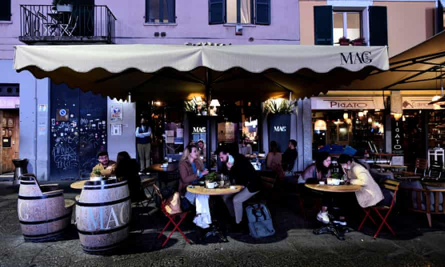 People sit outdoors at a cafe in Milan.