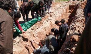 Syrians dig a grave to bury the bodies of victims of a chemical attack in Khan Sheikhun, in Idlib.