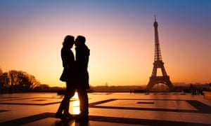 A couple kissing near the Eiffel Tower at sunset