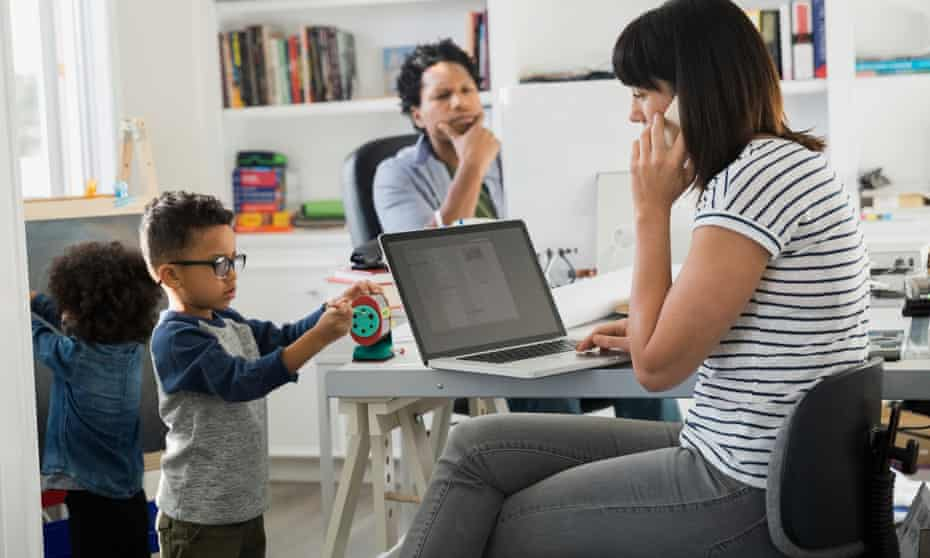 Parents working in home office with children playing