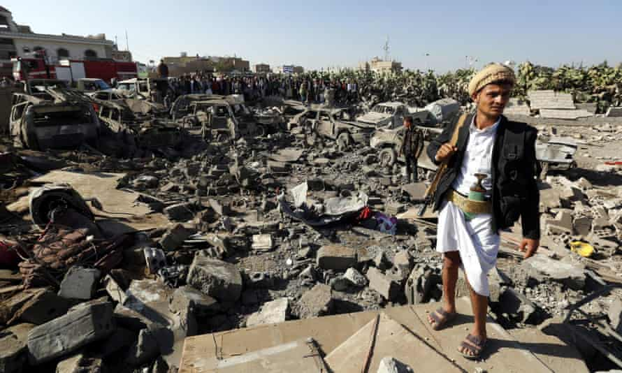 A Houthi rebel keeps watch as people gather beside vehicles allegedly destroyed by a Saudi air strike in Sana'a, Yemen.