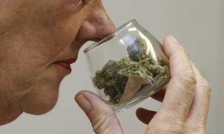 A customer checks the aroma of a jar of medicinal marijuana at Canna Care, a medical marijuana dispensary in Sacramento.