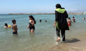 A woman wearing a burkini paddles on the seashore in Marseille, southern France. Photograph: AP