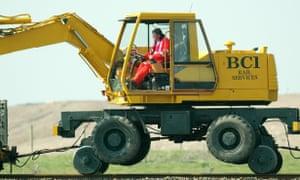 Man operates plant on railway line