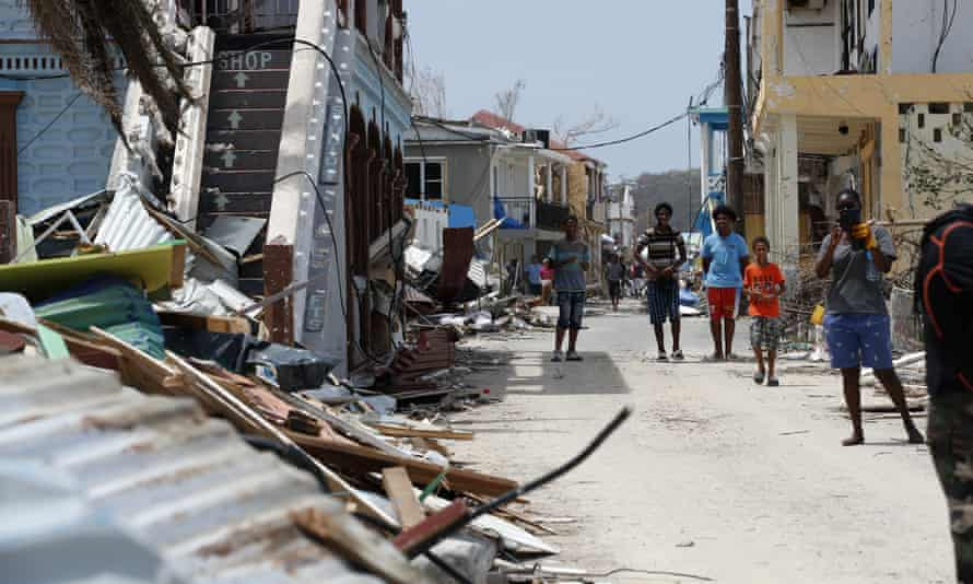 Residents wait in front of the houses destroyed by Irma during Emmanuel Macron's visit to St Martin on Tuesday, 12 September.