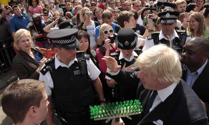 Johnson talks to a volunteer cleaning up damage from riots in 2011 in Battersea, south-west London