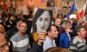 People holding photos of Daphne Caruana Galizia during a rally in Valletta.