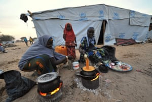 Nigerian refugee women cook in a United Nations Refugee Agency (UNHCR) refugee camp in Baga Sola by Lake Chad, which borders Chad, Nigeria, Niger and Cameroon, on January 26, 2015. Since the beginning of January more than 14,000 people have fled over the Nigerian border into Chad to escape the bloody attacks by Islamist group Boko Haram around Baga.