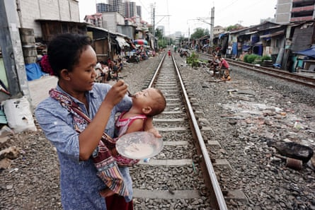 Indonesian woman feeds child