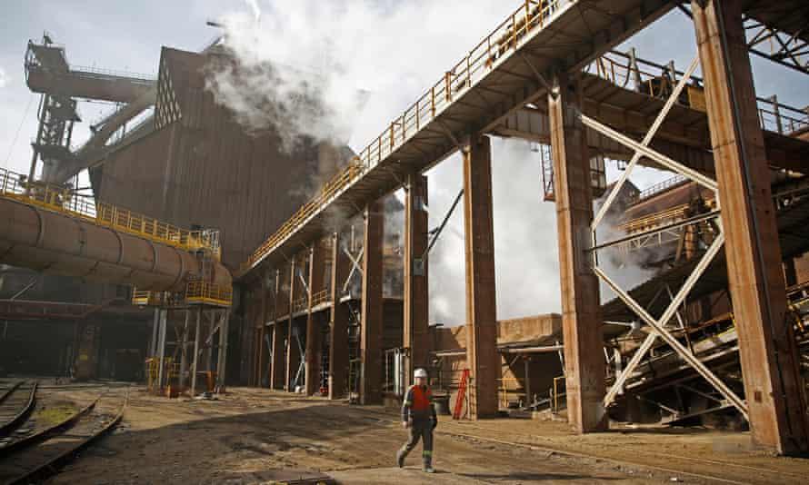 A worker walks in front of ArcelorMittal steel factory.