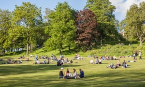 People enjoying a sunny evening in Kelvingrove Park, Glasgow.