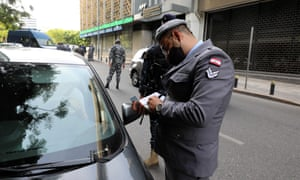 Lebanese policemen check cars at a checkpoint in the Sanayeh district of Beirut as the country went into lockdown