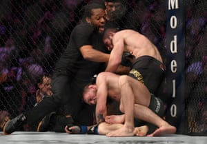 Referee Herb Dean separates Nurmagomedov and McGregor after the tap-out.