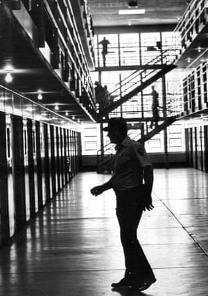 A guard crosses an open area in an old maximum security prison.