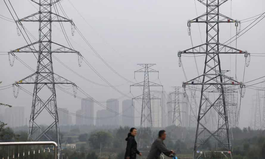 People walk past electricity pylons in Shenyang, China