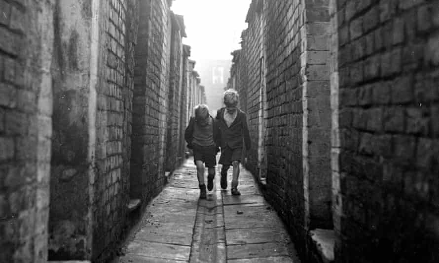 Two boys walking down an alley at the back of terraced houses in Manchester